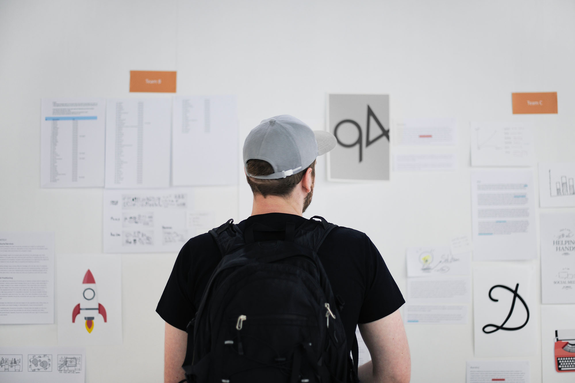 Man staring at whiteboard of logo ideas