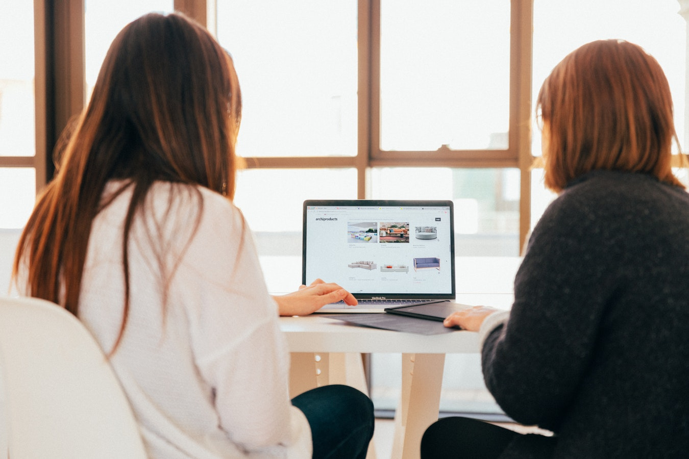 Two women sitting in front of a laptop
