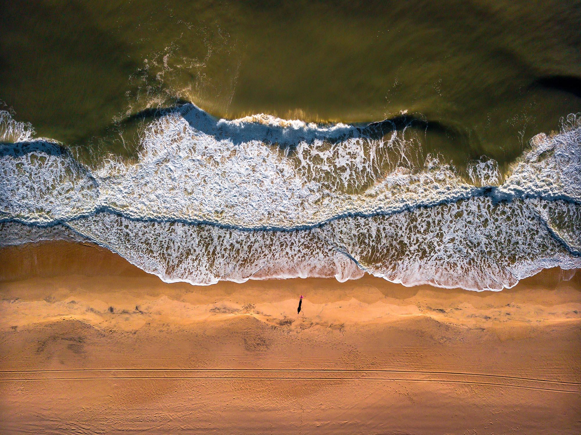 man standing in front of the ocean in ocean city maryland