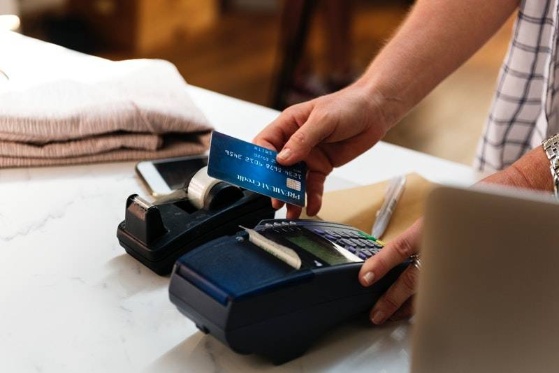 How to Get a Credit Card With No Credit: Hand pressing button on credit card machine