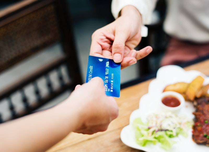 How to Get a Credit Card With No Credit: Person passing credit card to another person