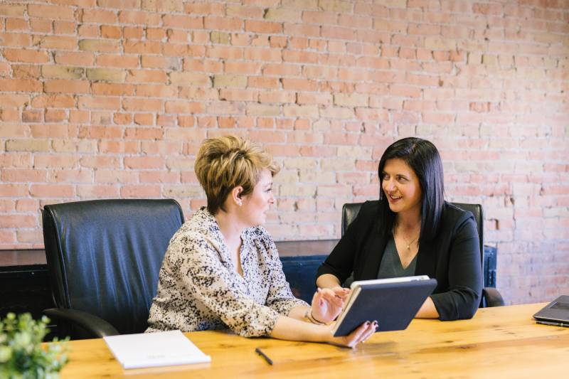 What Does a Financial Advisor Do: Two women sit at a table gesturing to a document