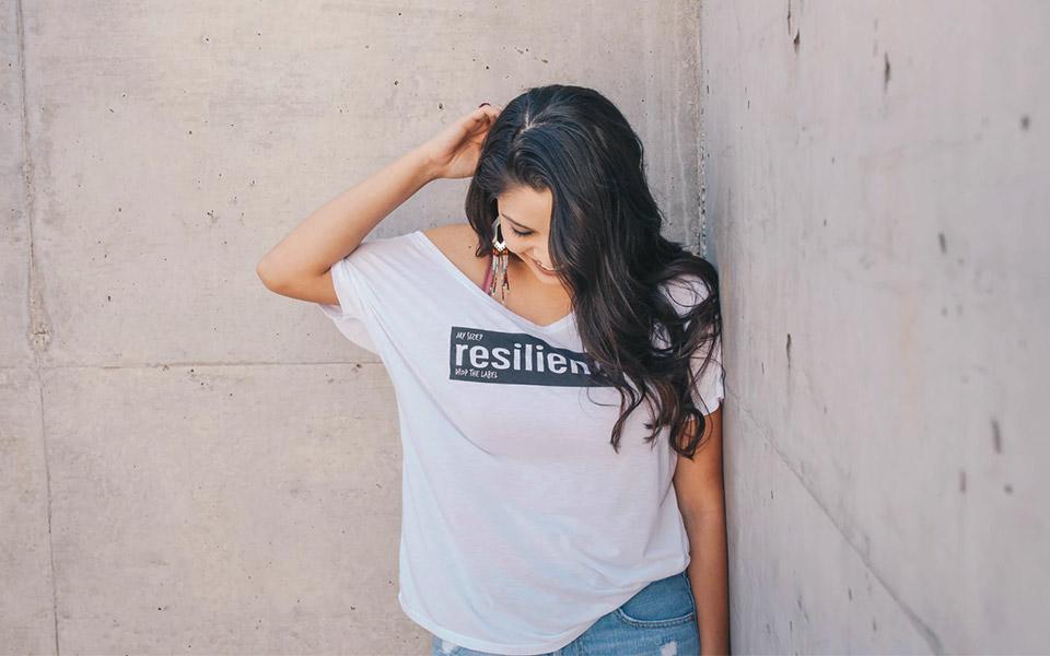 Weibliches Model trägt weißes V-Neck-Shirt mit schwarzem Aufdruck