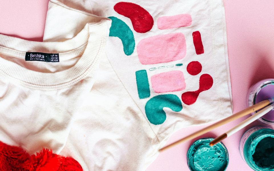 Bemaltes T-Shirt & daneben Pinsel und Farbe