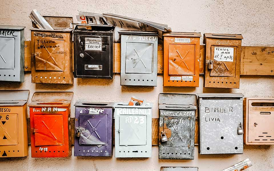 Diverse bunte Briefkästen eines Mehrparteienhauses