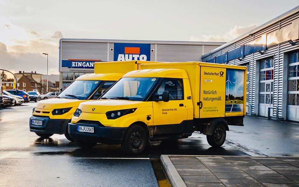 Zwei parkende Lieferwagen der Deutschen Post