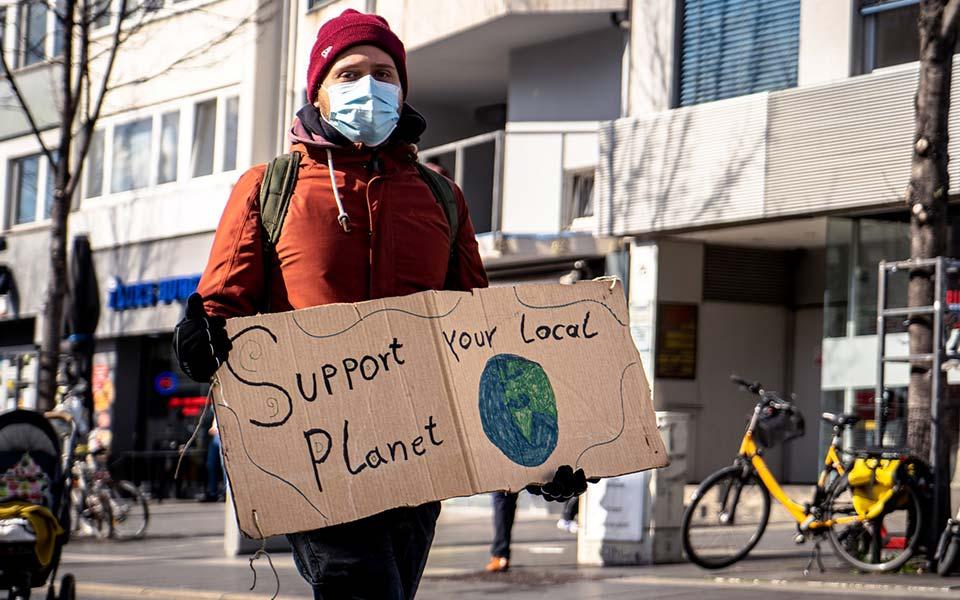 """Mann auf Demo mit Plakat """"Support your local Planet"""""""
