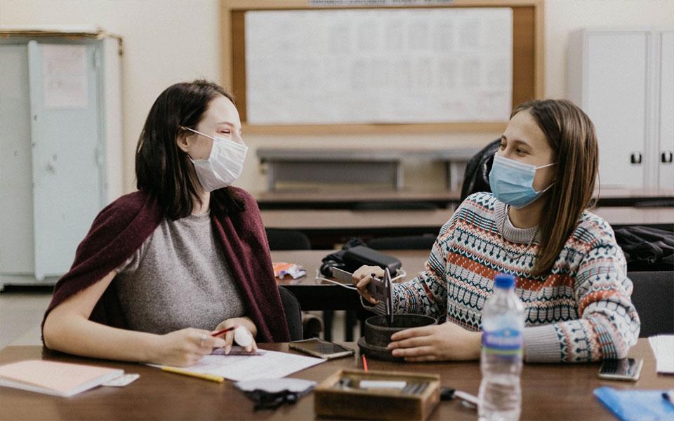 Zwei Schülerinnen mit Masken im Klassenzimmer