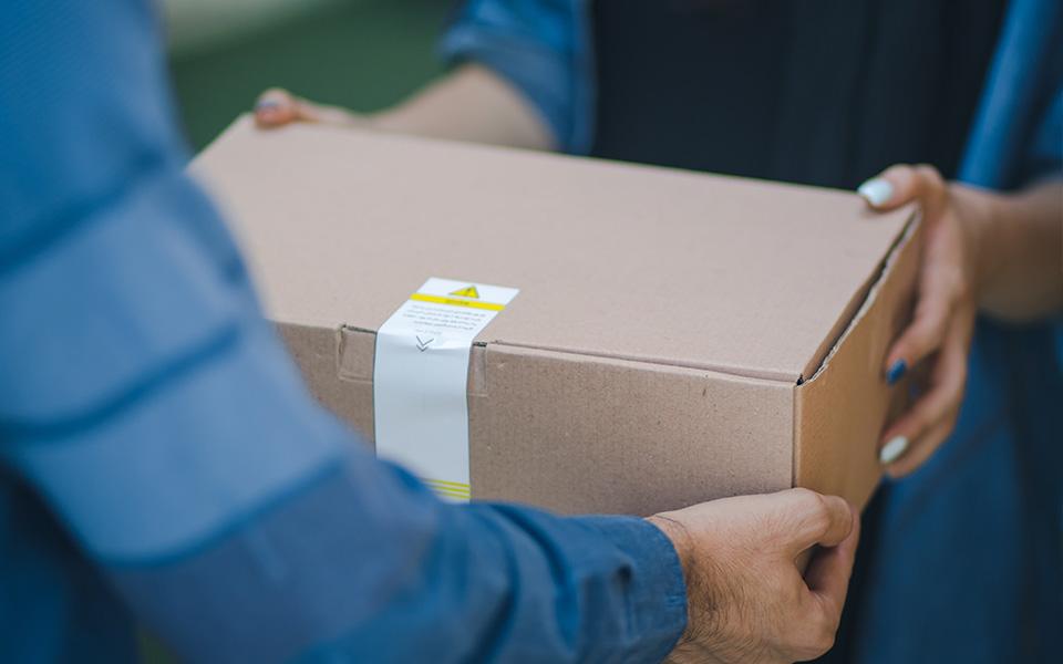 Paketbote überreicht Kunden Paket