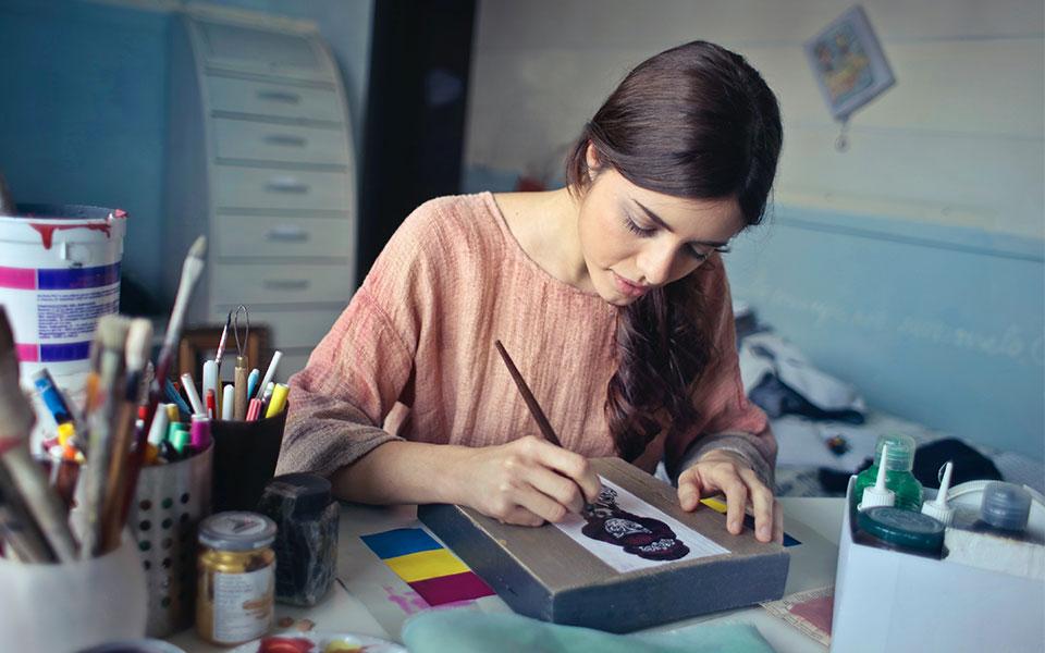 Frau malt Bild auf kleinem Holzblock
