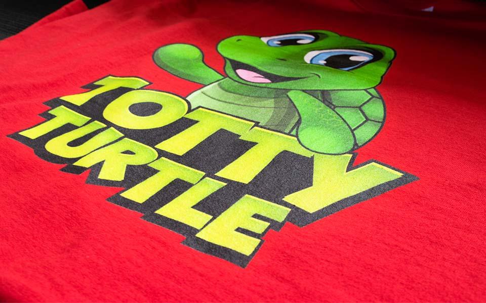 """Grüne Schildkröte mit Aufschrift """"Totty Turtle"""" auf rotem Shirt"""