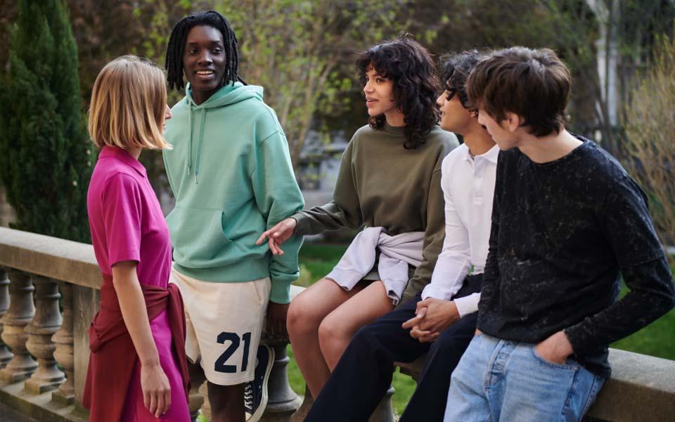 Junge Leute mit bunten Kleidungsstücken plaudern auf einer Brücke in der Natur