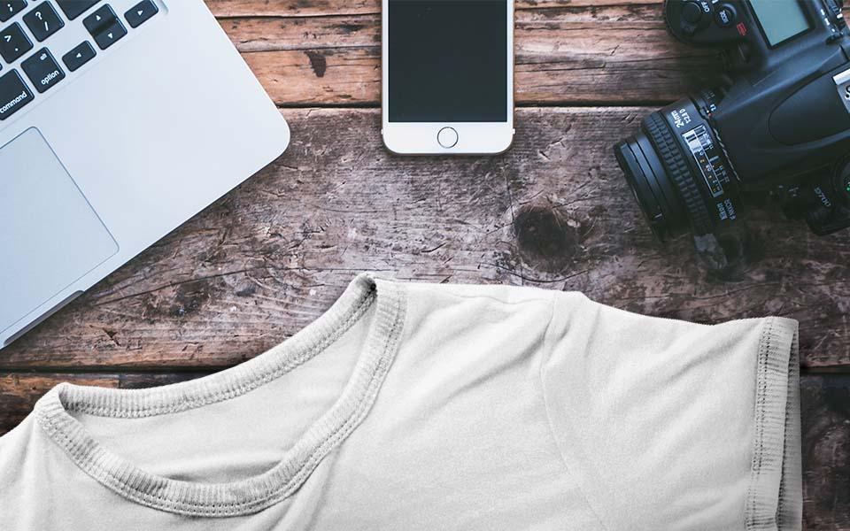 Ausschnitte von Laptop, Smartphone, Kamera und Shirt