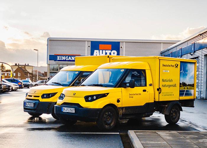 Zwei Deutsche-Post-Lieferwagen auf Parkplatz