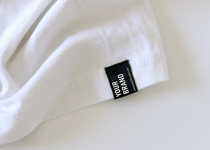 Weißes Textil mit Your-Brand-Web-Etikett am Saum