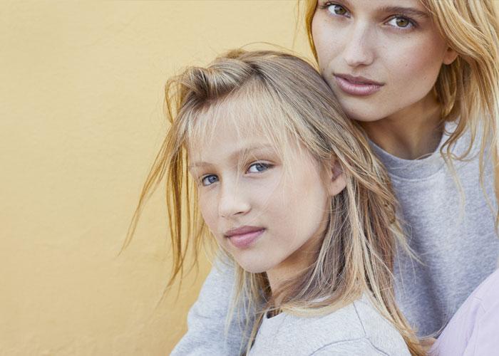 Junge Frau mit Kind trägt Organic-Sweatshirts