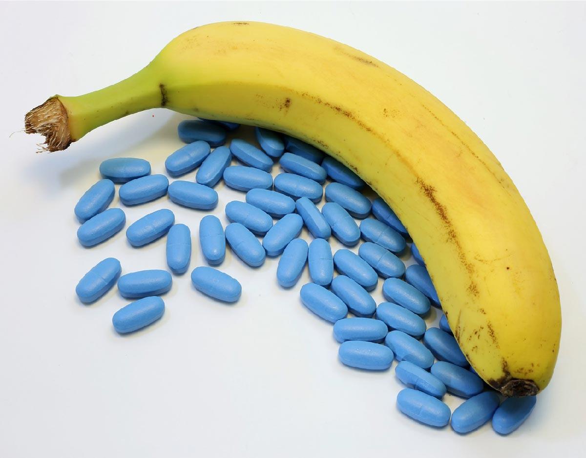 banana in primo piano con sotto delle pillole blu