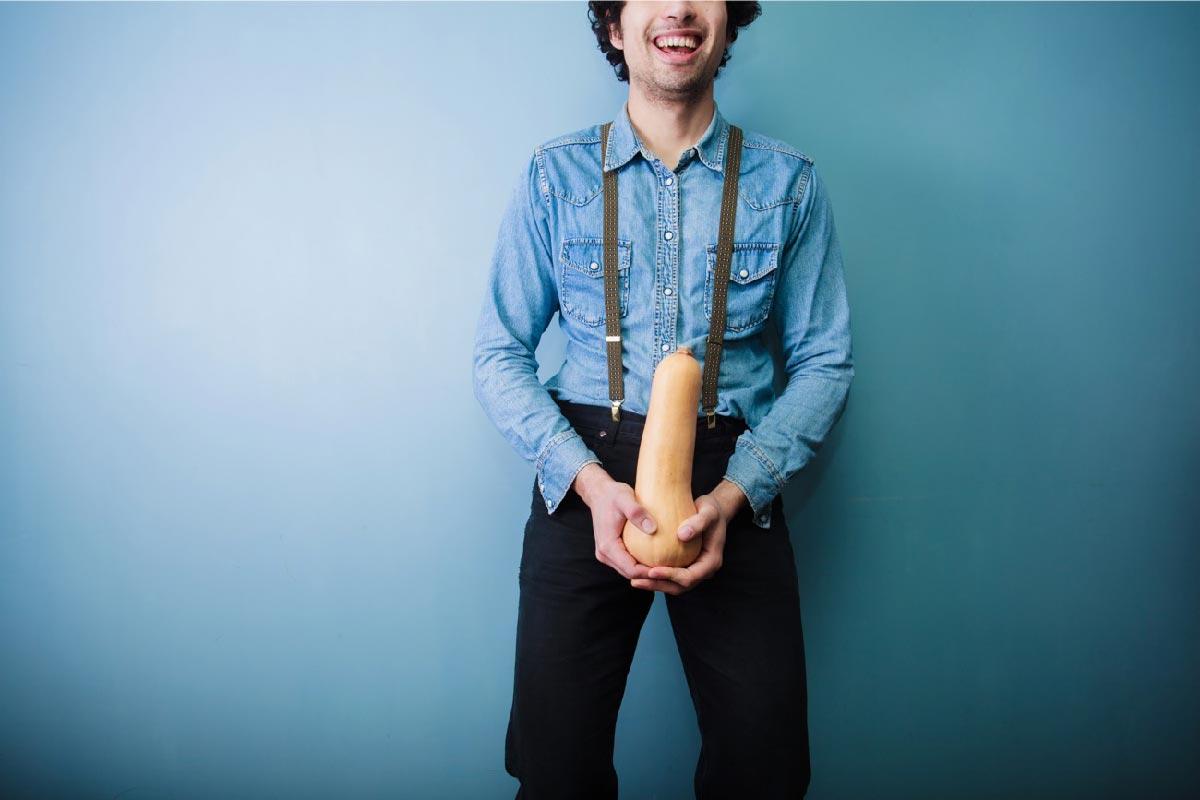 un uomo sorride tenendo una zucca
