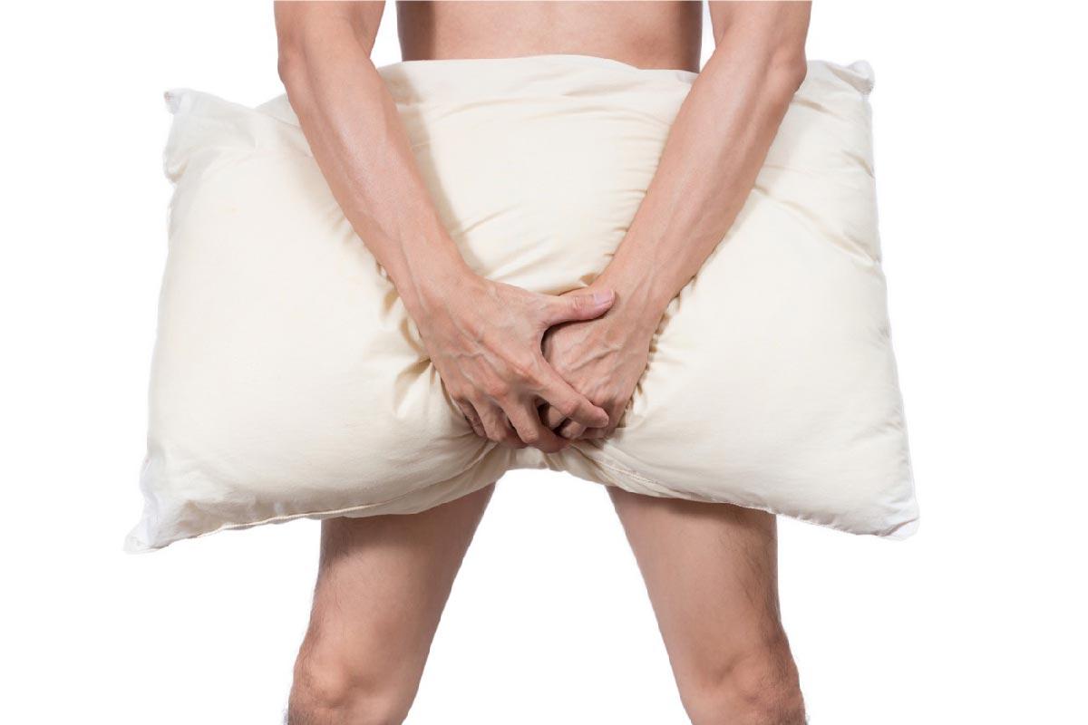 un uomo copre il pene con un cuscino