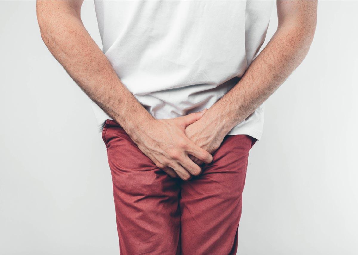 un uomo con pantaloni rossi si copre il pene