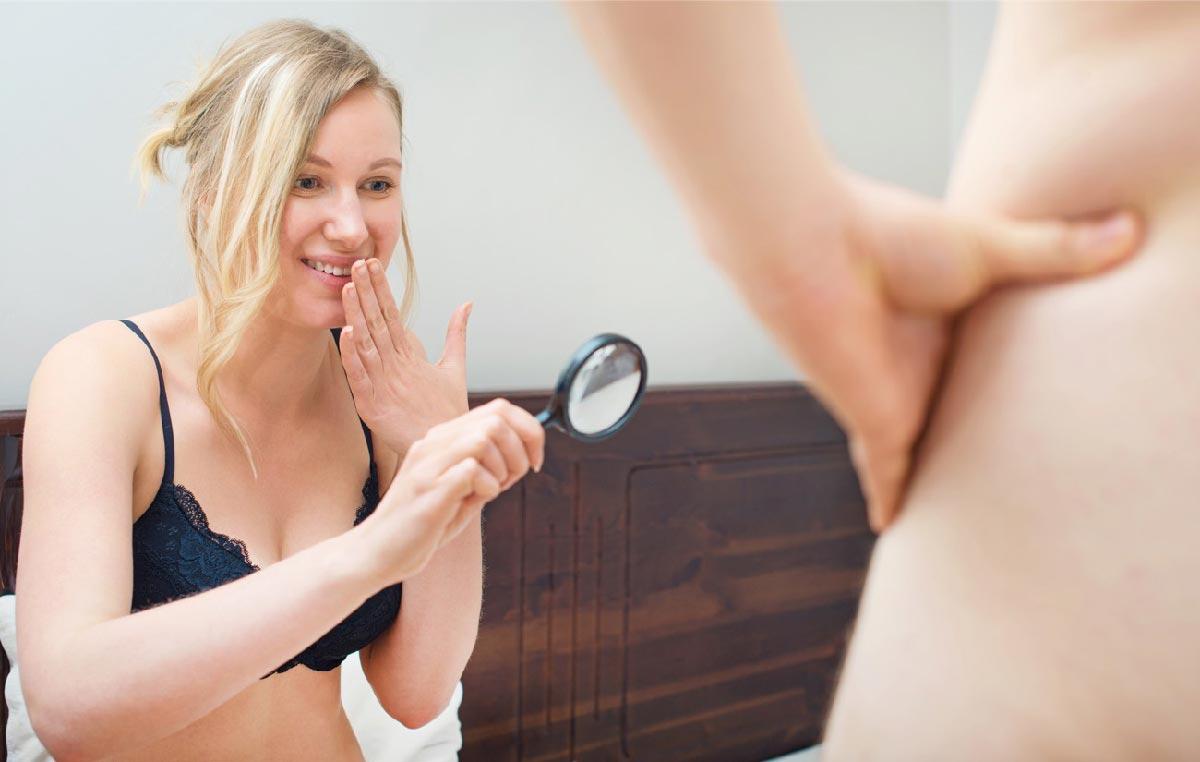 una donna con lente d'ingrandimento ride del suo partner