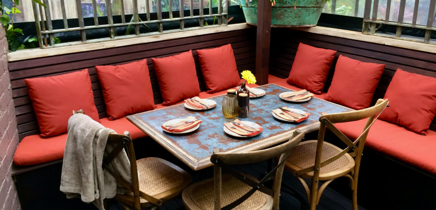 Garden shed dinner table with red cushions.