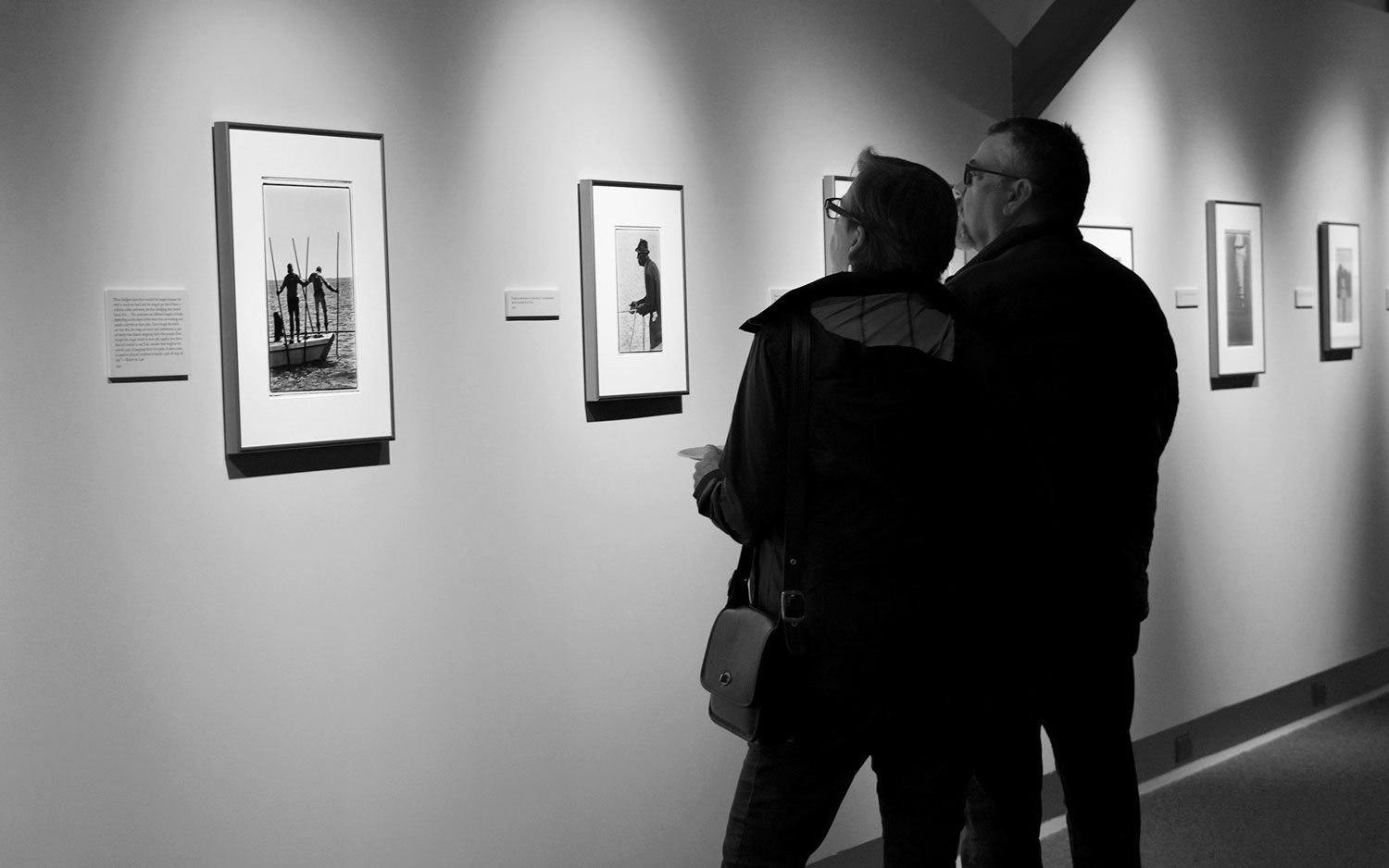 man and woman viewing photographs in an exhibition