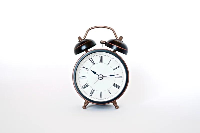 White alarm clock on a white background.
