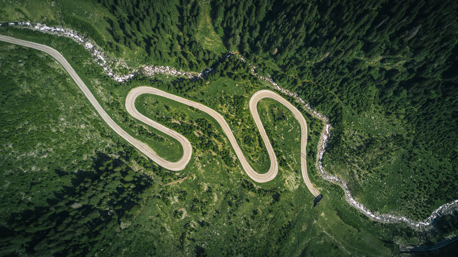 Aerial view of a winding roadway through the mountains.