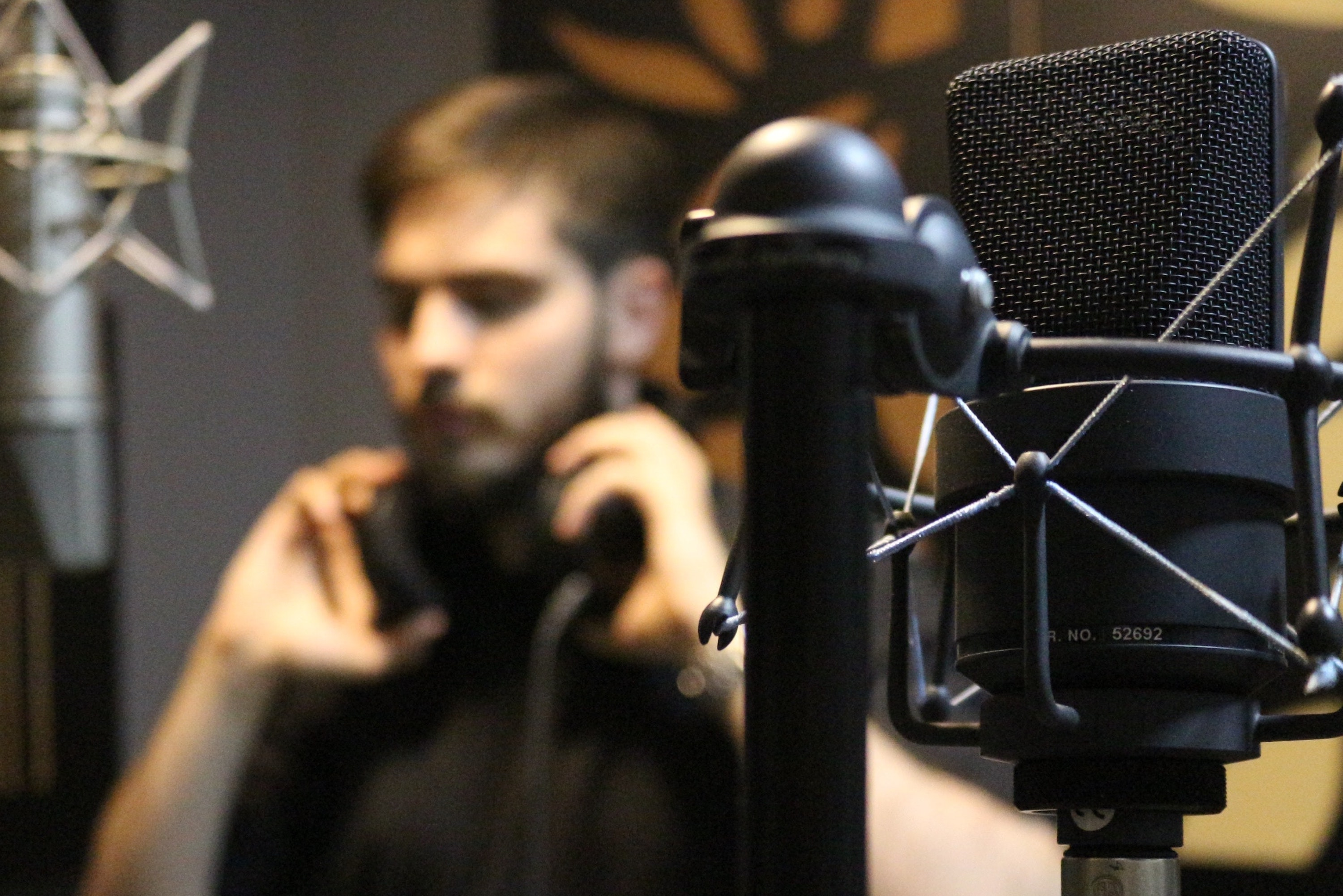 Condenser microphone in a studio recording environment with a singer.