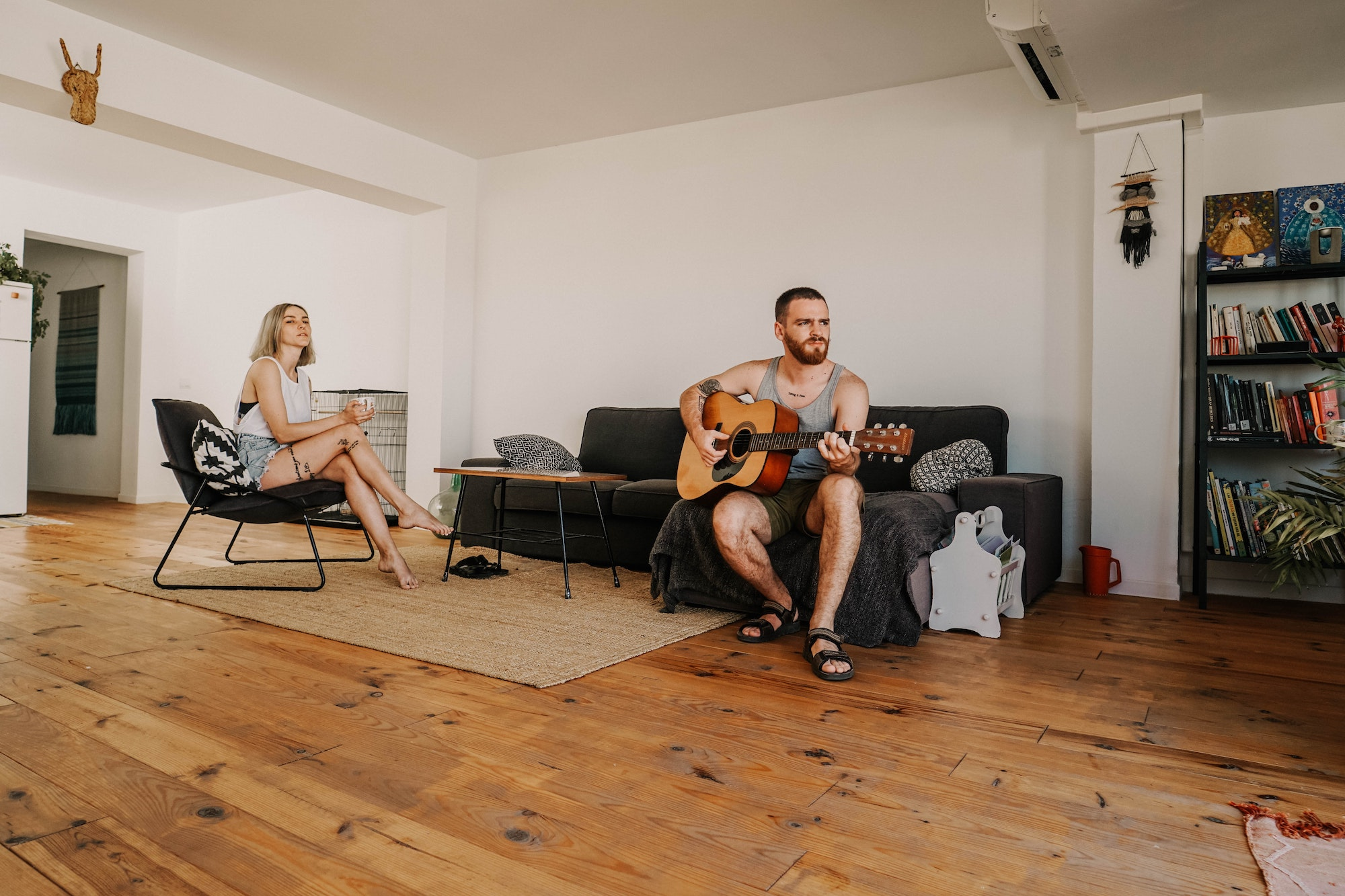 Two songwriters writing a song in the same room. One is holding a guitar.