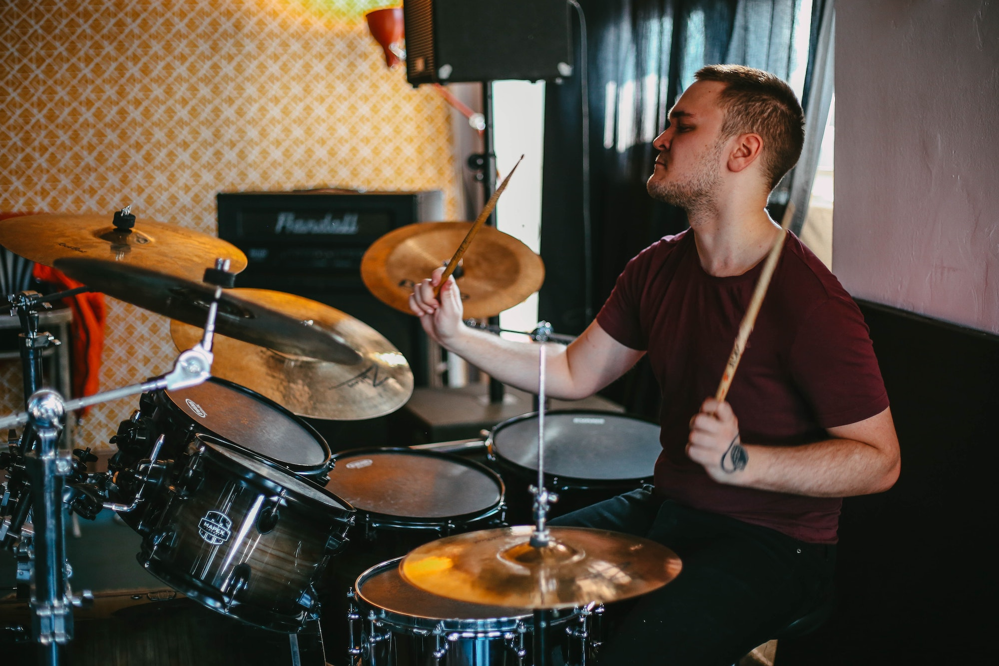 Young man playing an acoustic drum kit and hitting the crash cymbal.