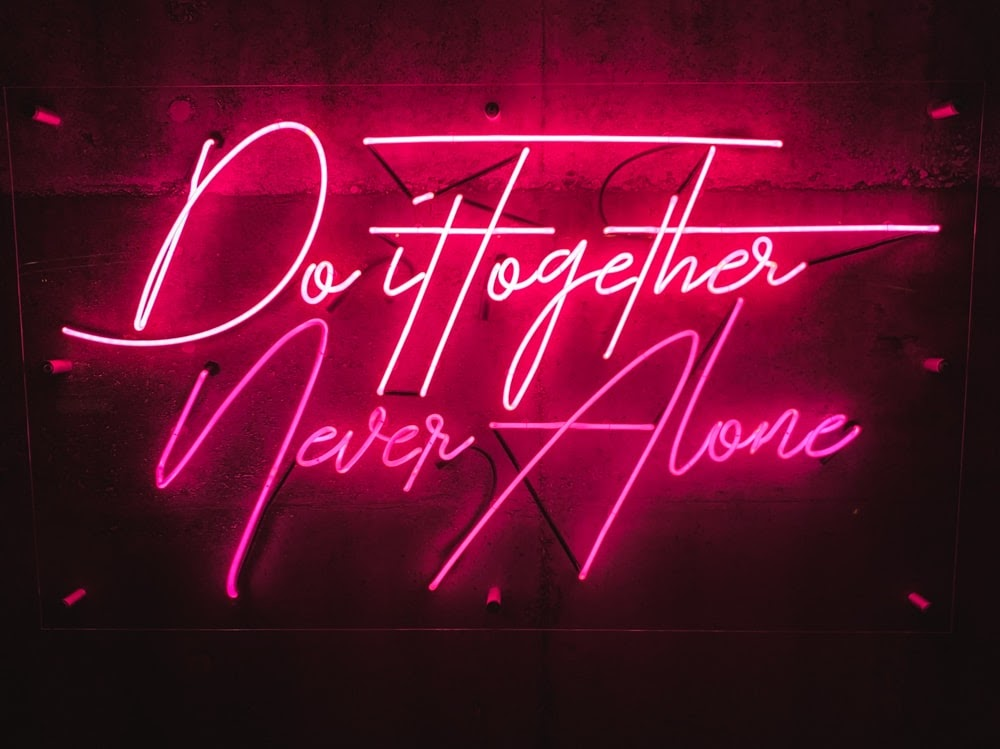 """Red neon sign that says """"Do it together, never alone."""""""