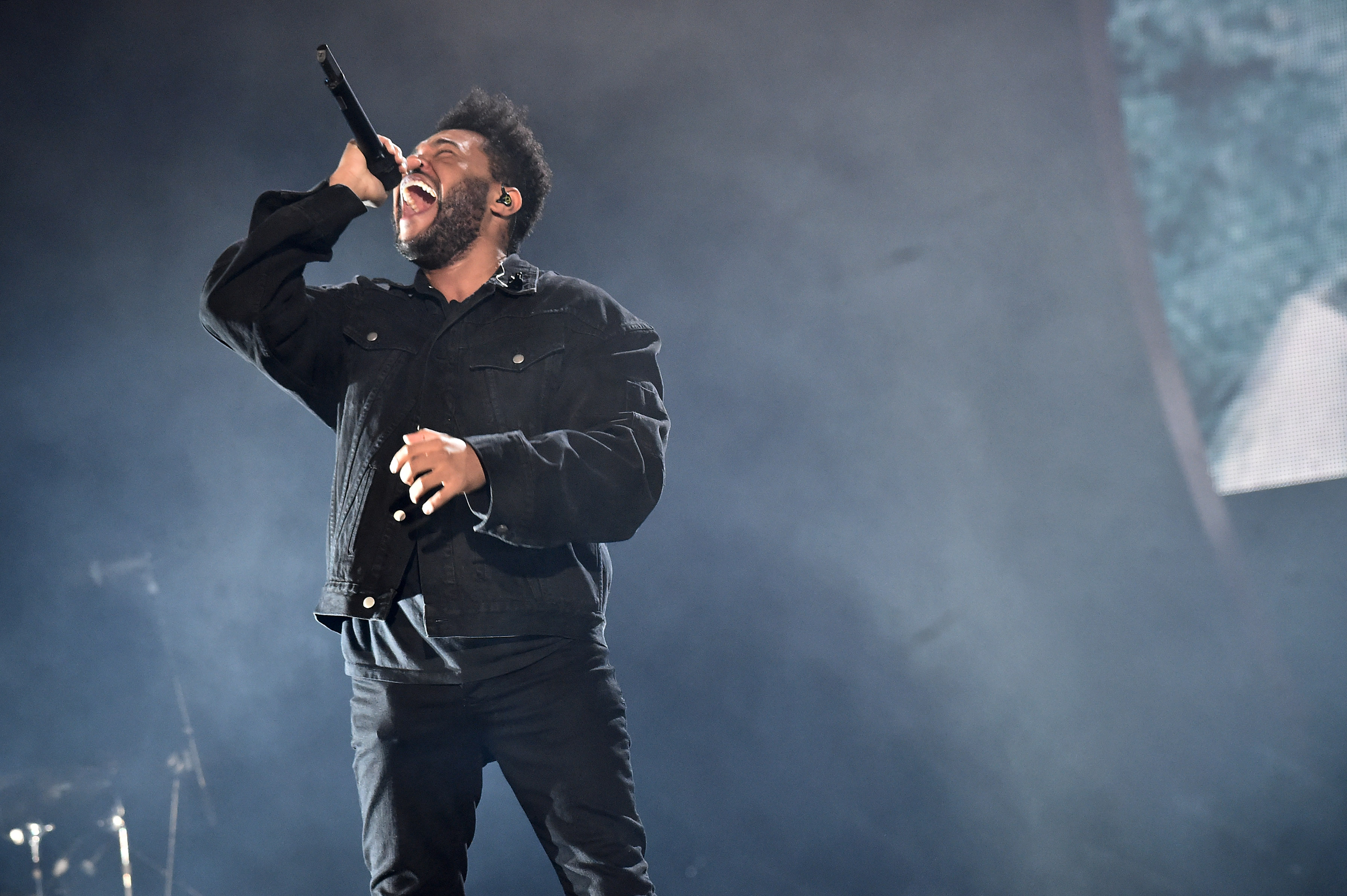 The Weeknd performing live wearing an all black outfit and singing into a wireless microphone.