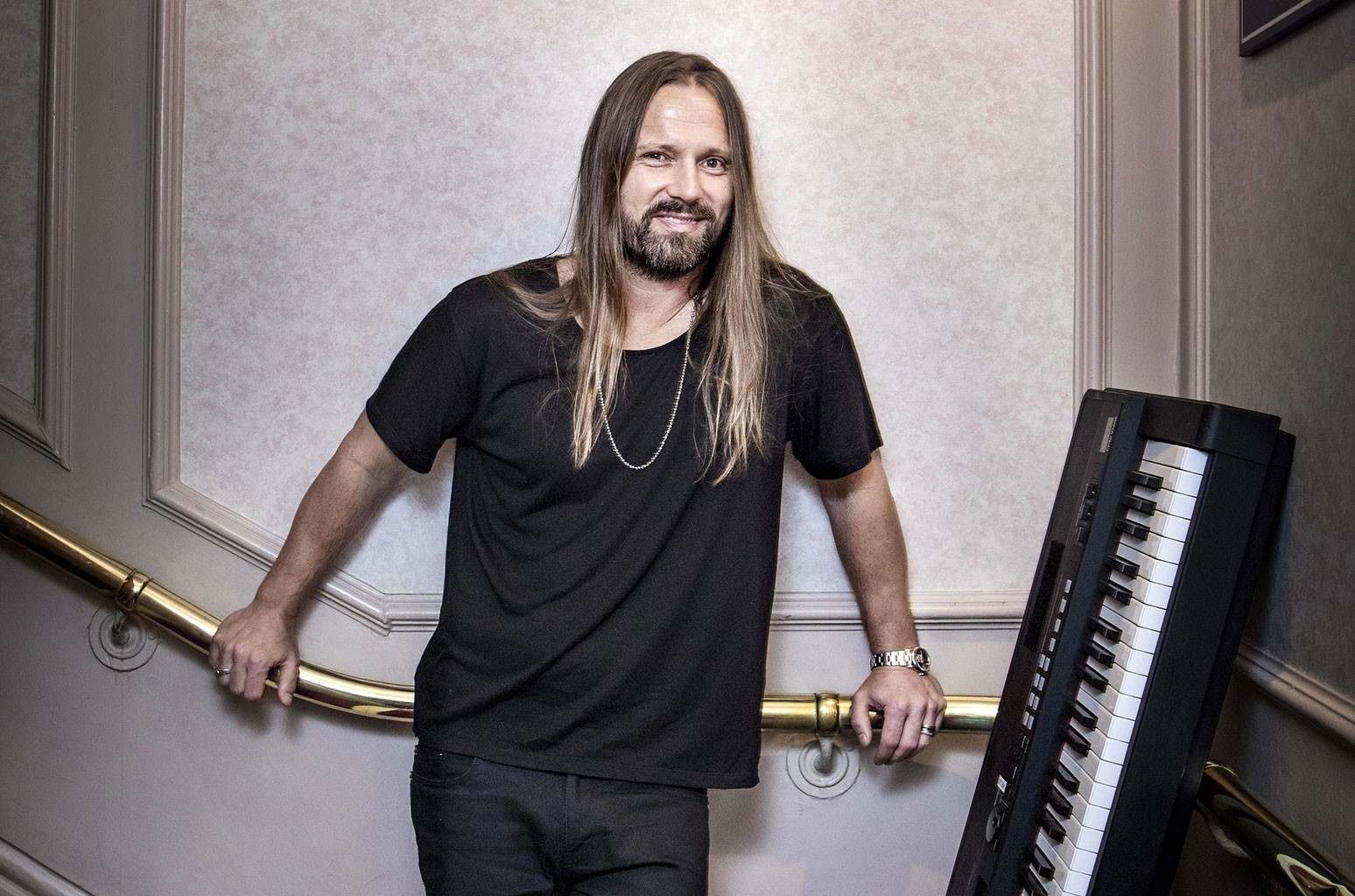 Max Martin standing in a hallway with a large keyboard next to him.