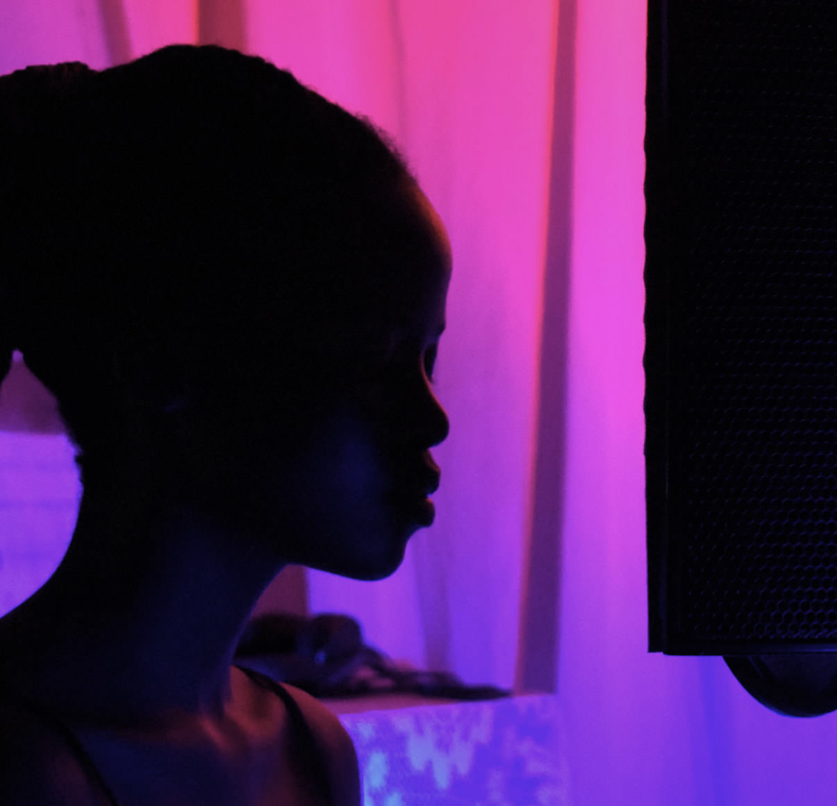 Girl recording in a studio next to a microphone