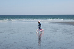 Girl Cycling on the Beach