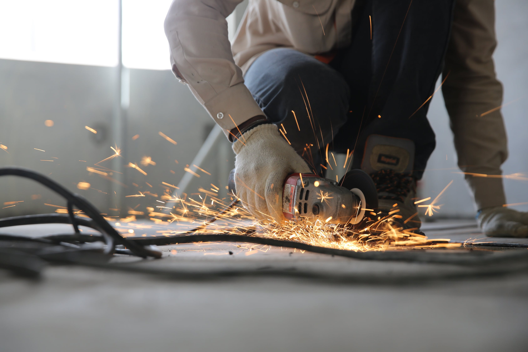 worker using grinding and cutting tools for construction project