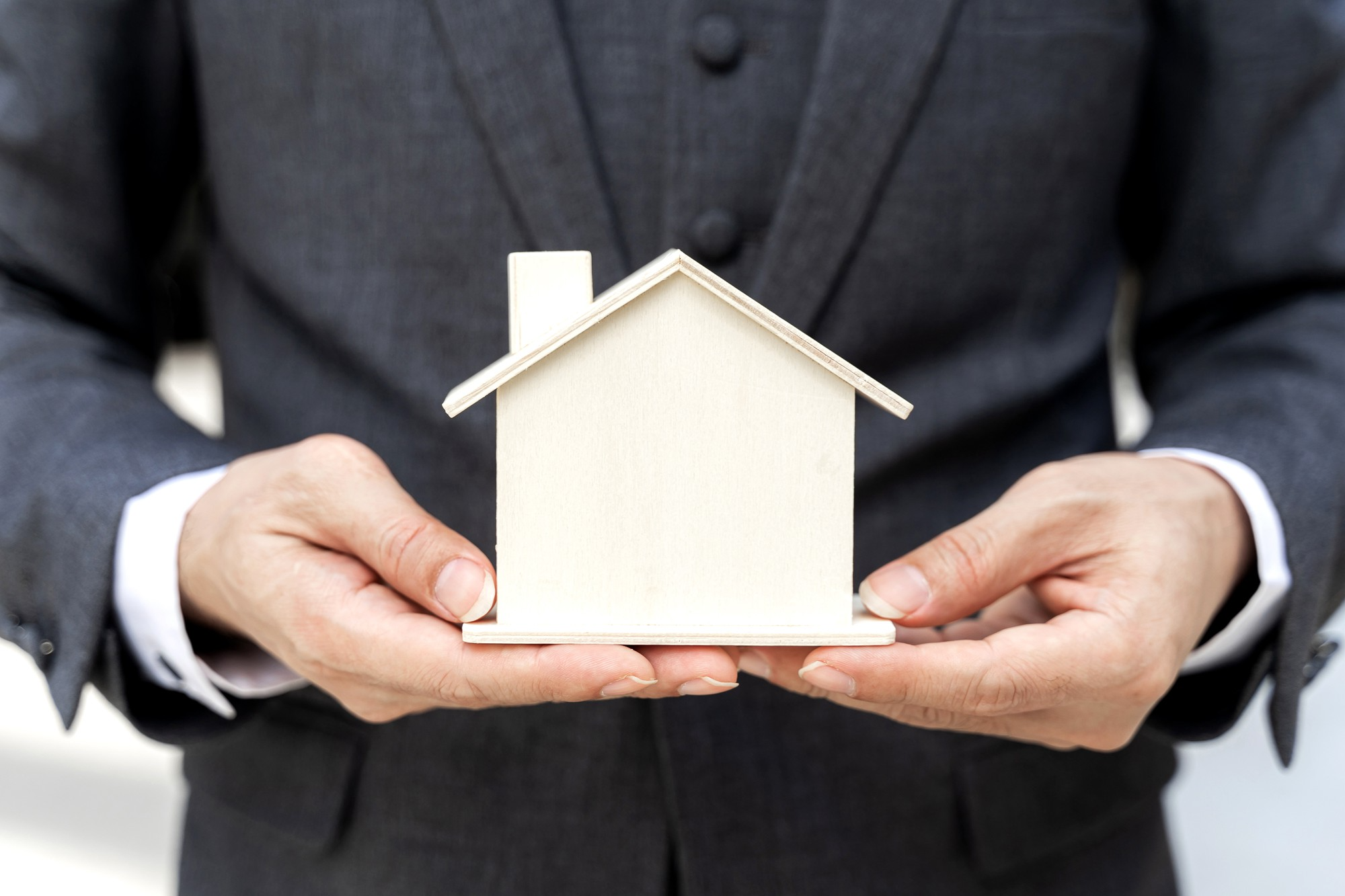 man holding scale wooden model of a house