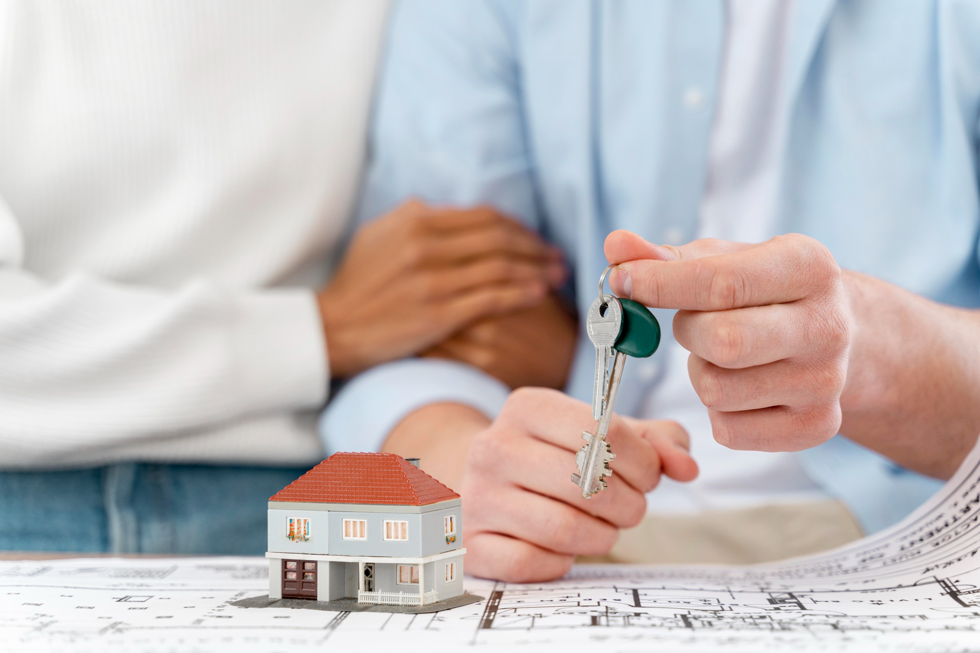 couple holding keys to new home with scale model and blueprints in front