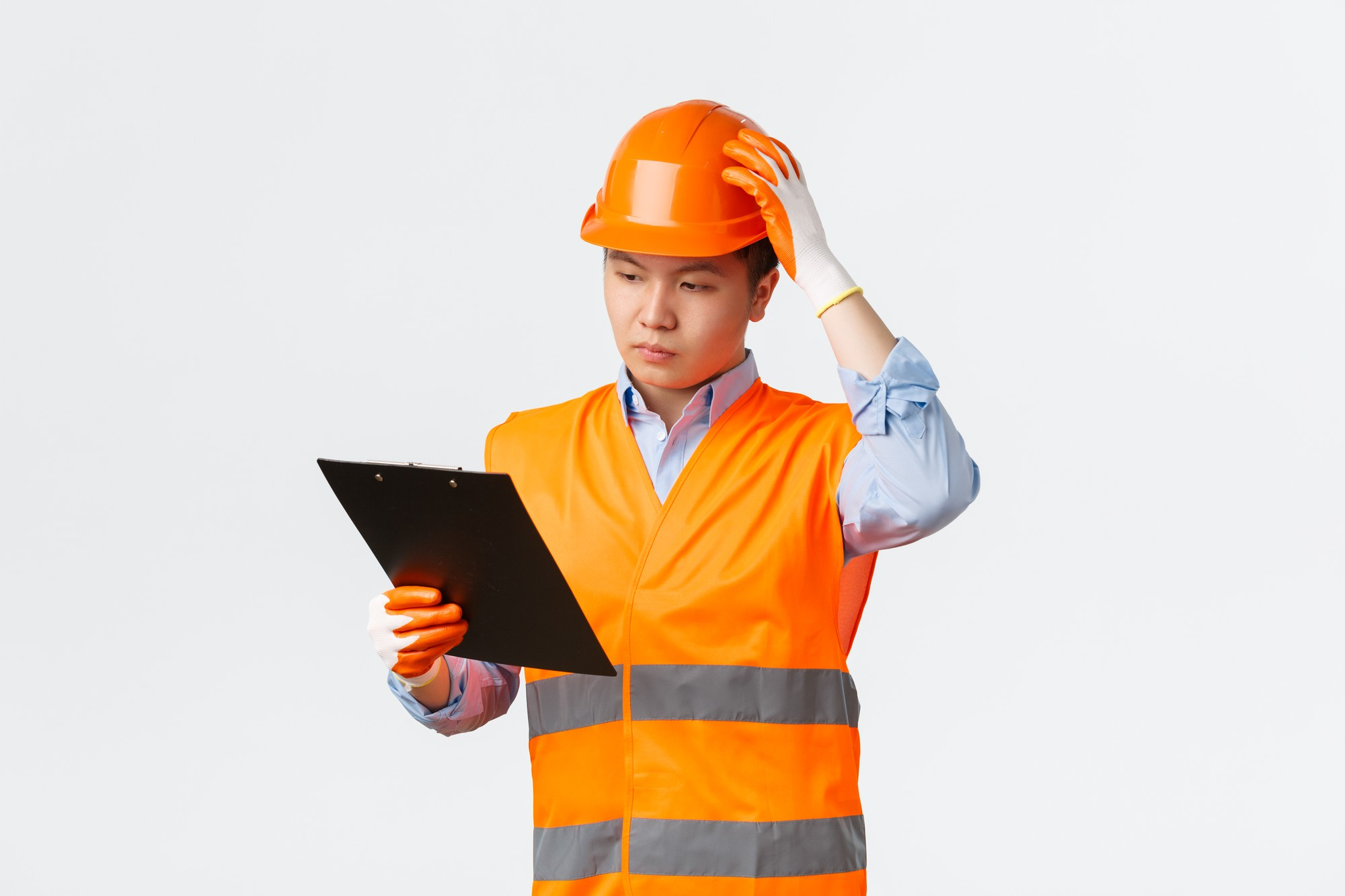 young engineer looking at clipboard holding hard hat