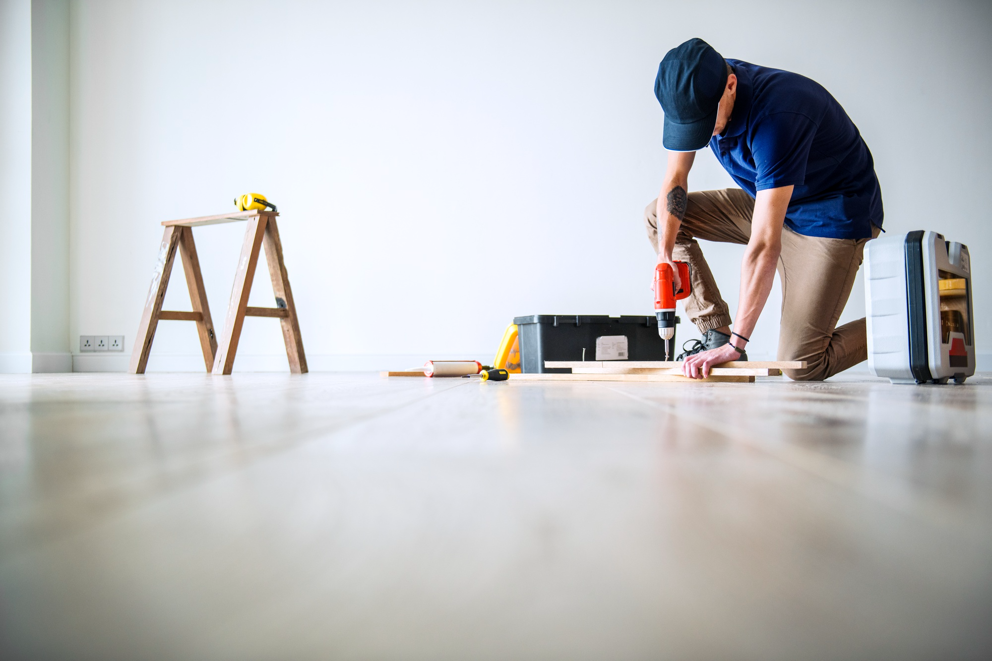 man drilling wooden boards indoors