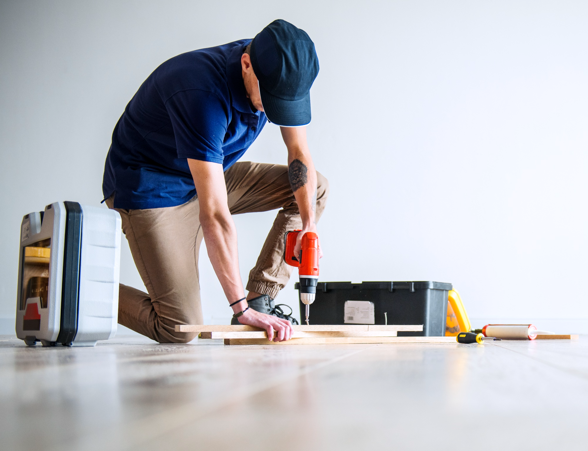 man drilling wooden boards inside home