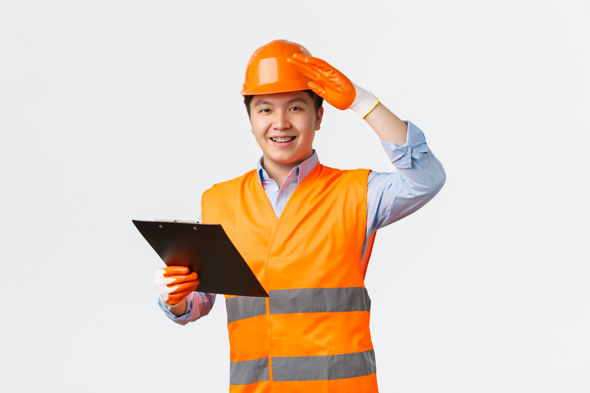 young engineer smiling and saluting while holding blueprint
