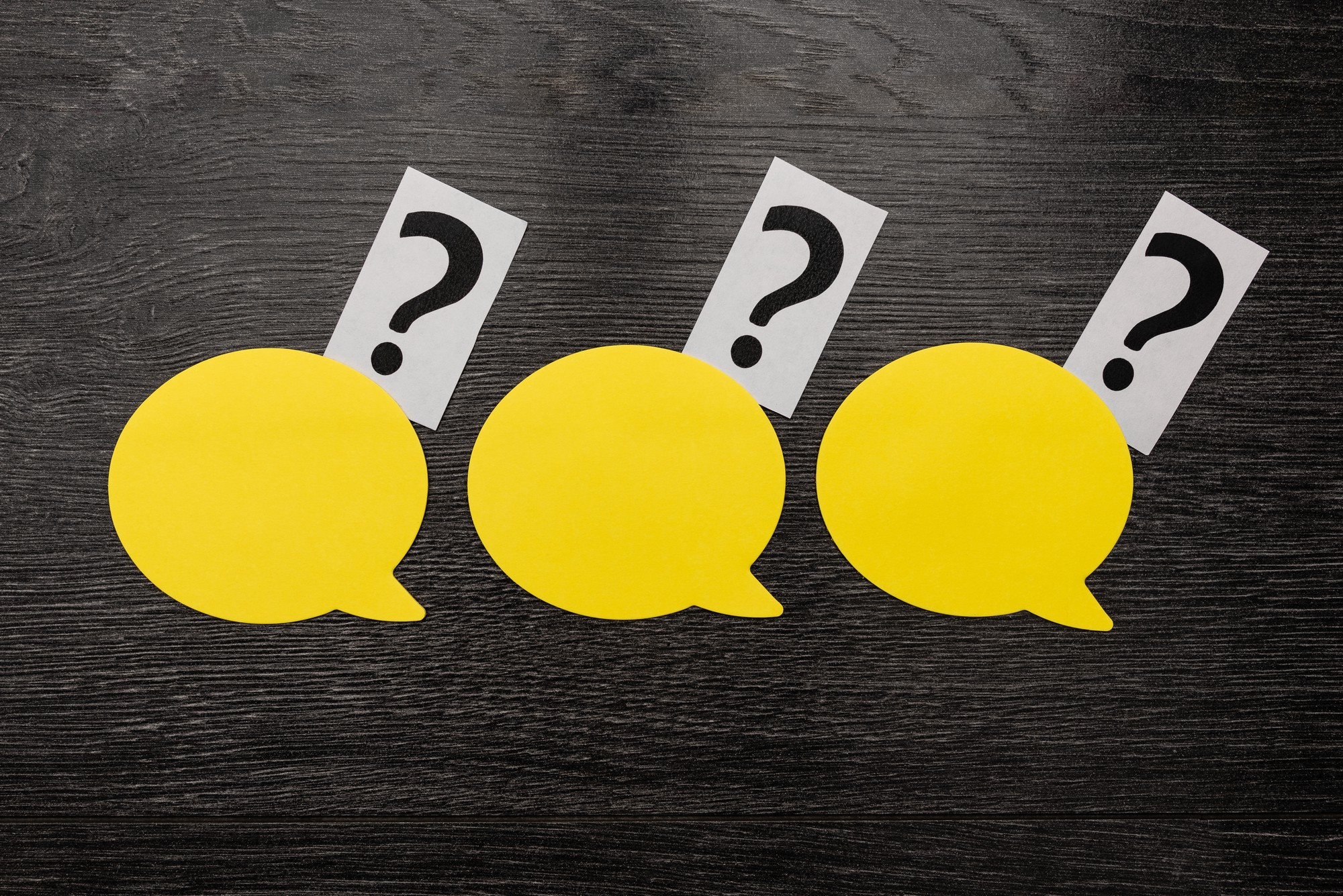 three yellow speech bubbles with question marks
