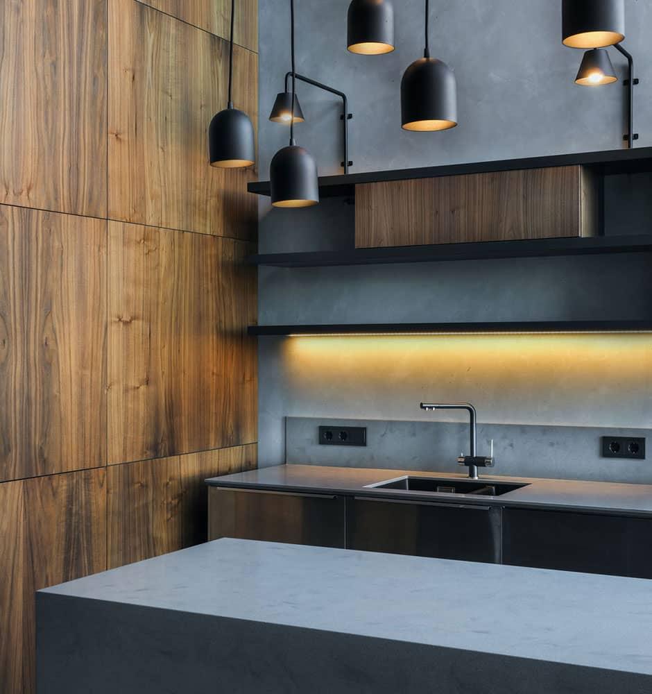 Cuisine contemporaine asymétrique en béton, inox et bois avec lustre lumineux.