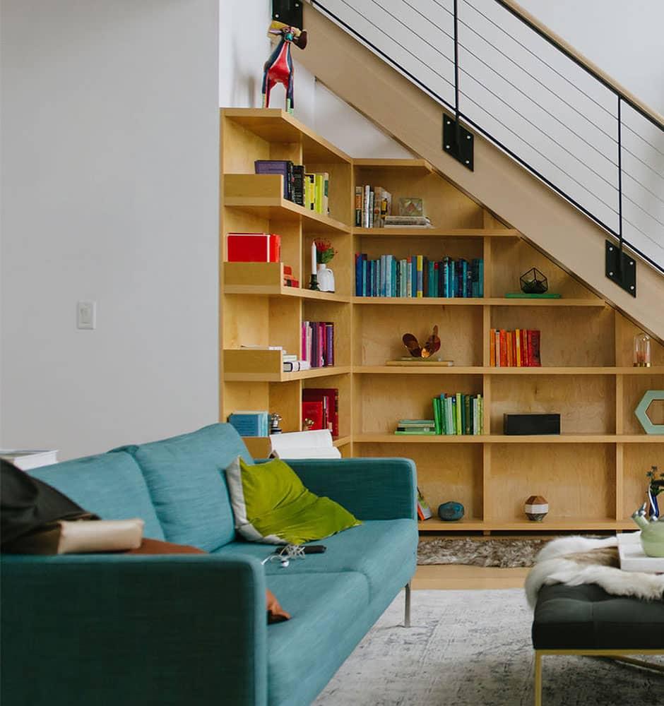 Bibliothèque et rangements ouverts en bois de chêne clair conçu sur-mesure sous escalier.