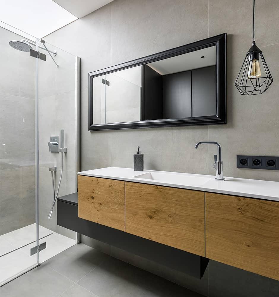 Meuble de salle de bain asymétrique sur-mesure noir et bois avec vasque en granite.
