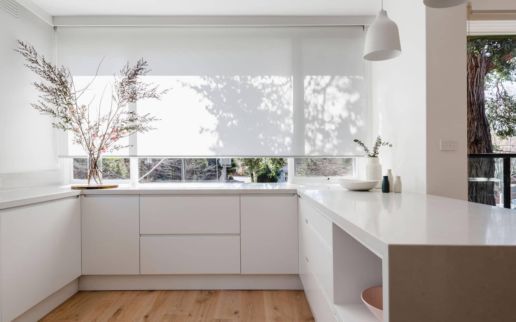 Cuisine contemporaine sur-mesure blanche avec plan de travail en granite.