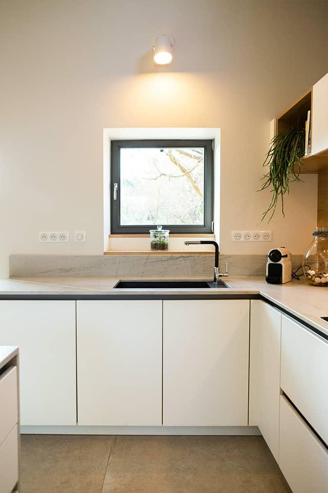 Projet de l'Atelier de Léa : focus sur les placards et l'évier d'une cuisine contemporaine minimaliste blanche sur-mesure.